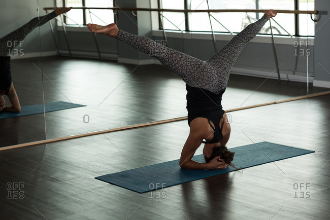 Woman practicing yoga on exercise mat