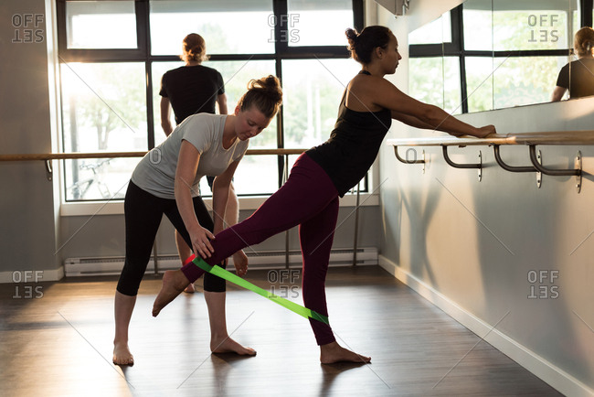 Trainer assisting woman to exercise with resistance band
