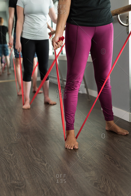 Low section of women exercising with resistance band