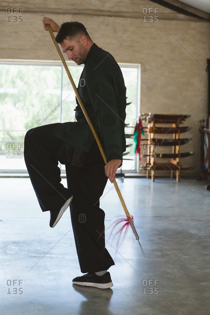 Kung fu fighter practicing with long pole