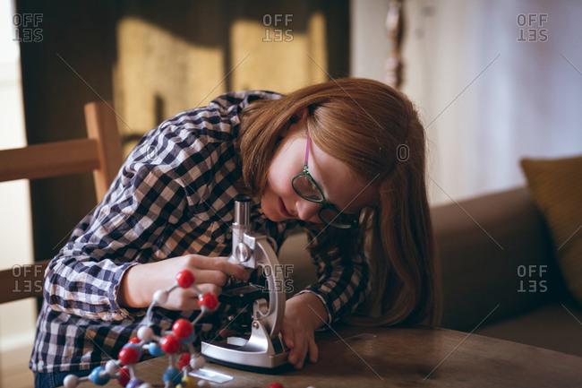 Girl experimenting molecule on microscope