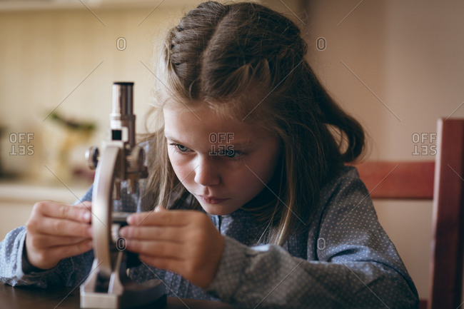 Girl experimenting with microscope