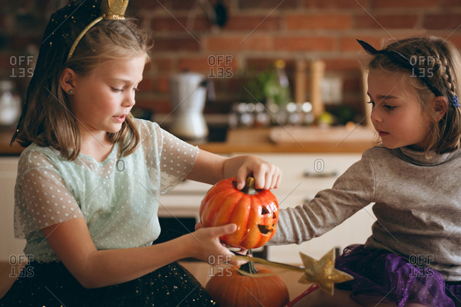 Sisters carving pumpkin in kitchen