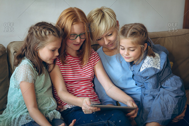 Mother and her kids using digital tablet at home