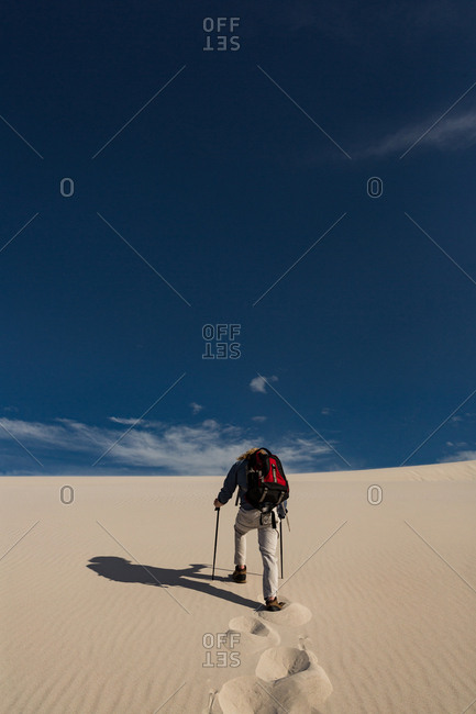 Hiker with trekking pole walking on sand