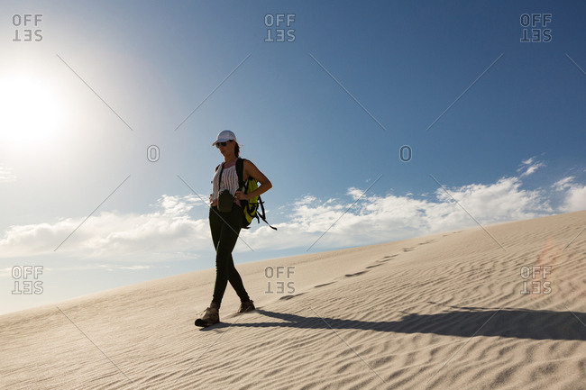 Female hiker with backpack walking on sand