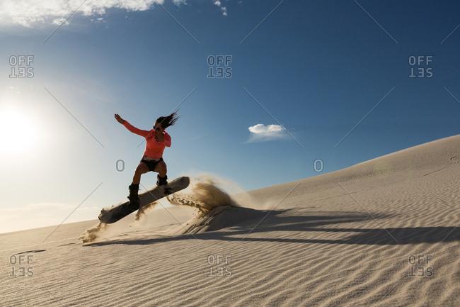 Man sandboarding on sand dune