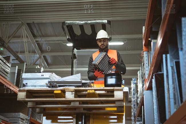 Male worker checking machine part