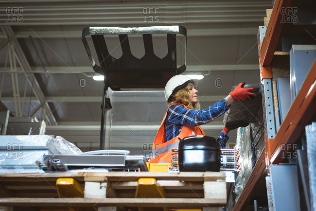 Female worker unloading machine part from rack