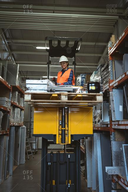 Female worker checking machine part