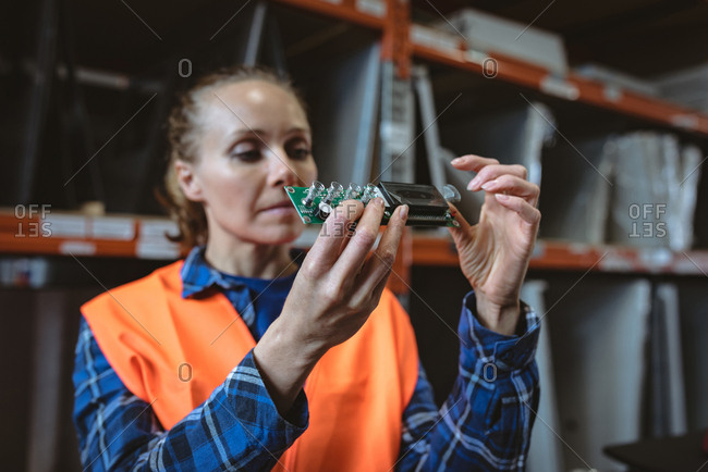 Female worker checking circuit board