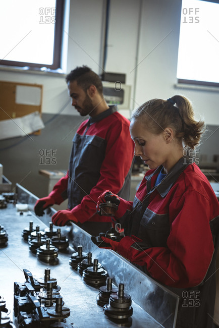 Two workers checking machine parts