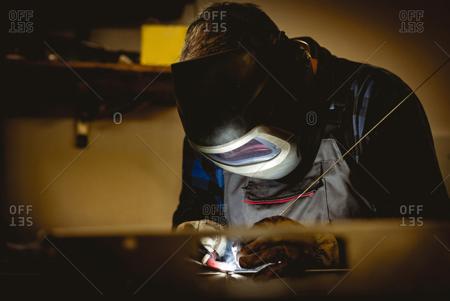 Worker working on manufactured metal parts