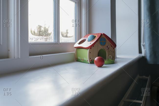 Wooden toy house left on windowsill