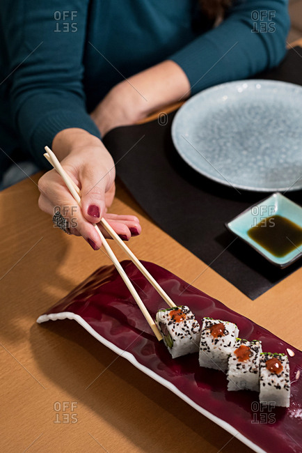 Crop shot of woman treating herself with delicious fresh sushi using chopsticks.