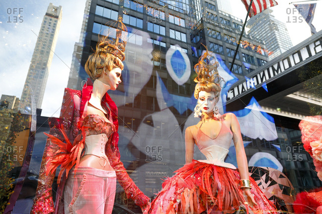 New York City, New York, USA - December 18, 2017: Buildings reflected in store window with mannequins