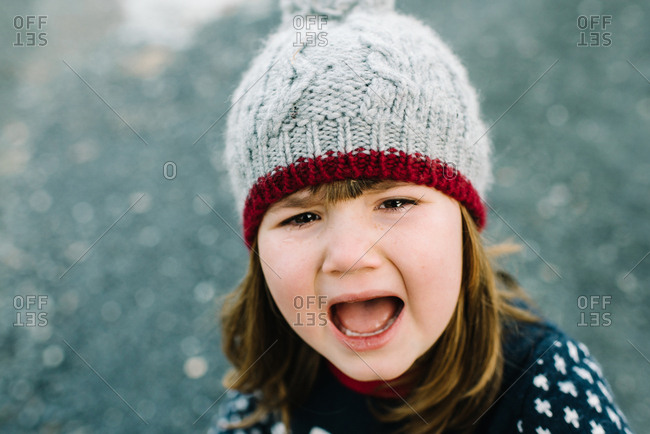 Portrait of a crying girl wearing a knit hat