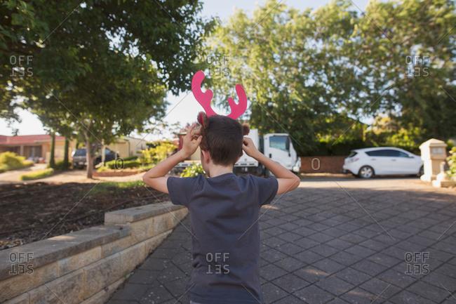 Boy putting on reindeer antlers costume