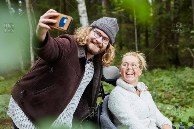 Young male caretaker taking selfie with disabled woman in forest