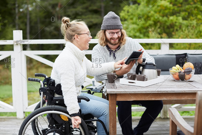 Young male caretaker and disabled woman using digital tablet in yard