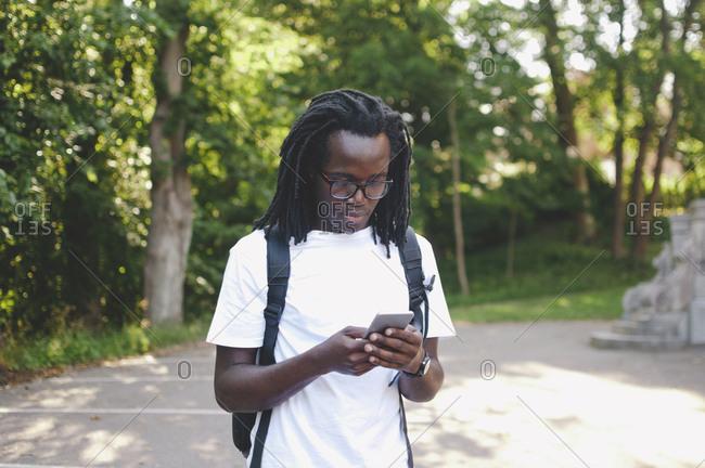 Young university student using mobile phone outside university