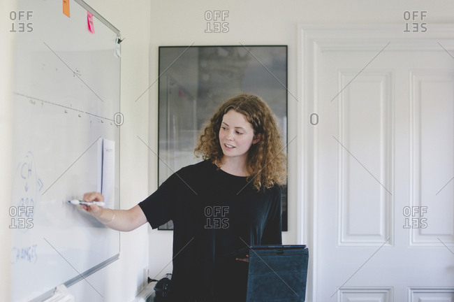 Young businesswoman giving presentation in creative office