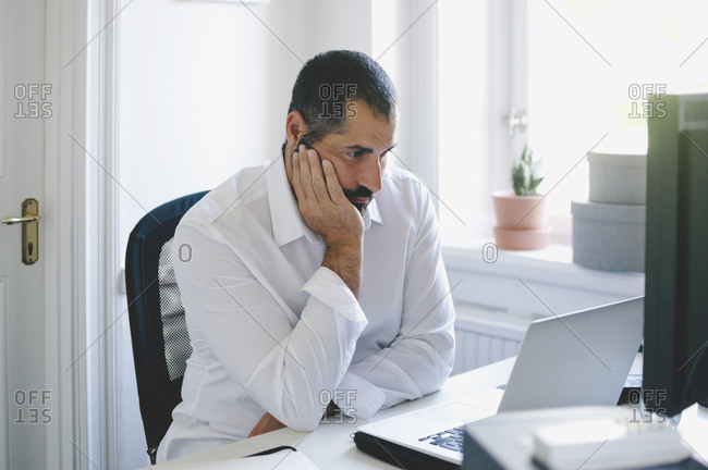 Mature businessman with hand on chin looking at laptop in creative office