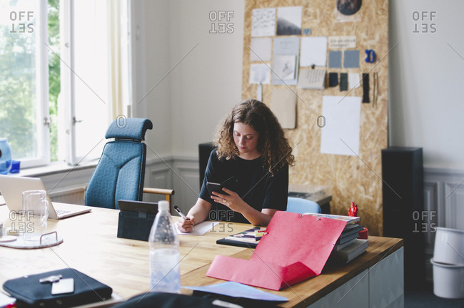 Young businesswoman using mobile phone while writing on paper at desk in creative office