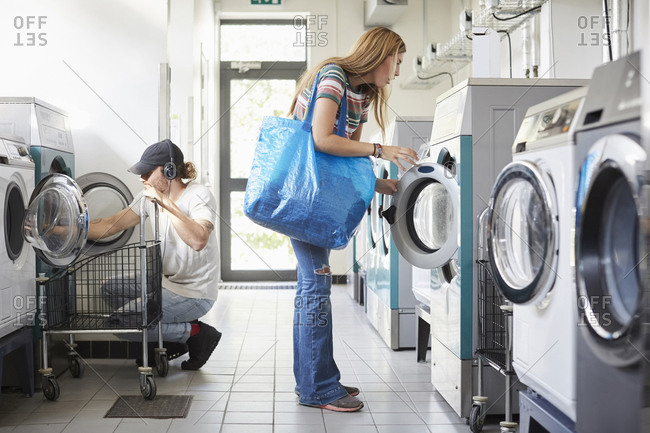 Full length of male and female university students doing laundry at laundromat