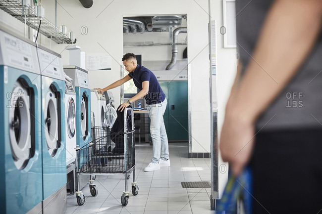 Full length of man using washing machine at laundromat with friend standing in foreground