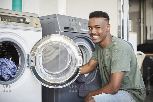 Portrait of smiling young man kneeling by washing machine at laundromat
