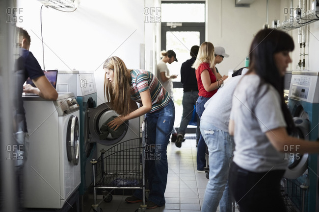 Multi-ethnic university students using washing machines in laundromat