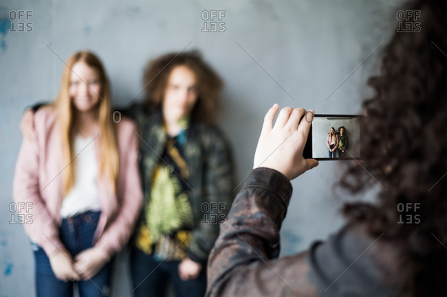 Teenage girl photographing friends standing against wall at parking garage