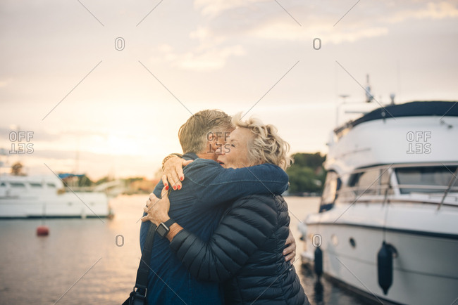 Side view of senior man and woman embracing at harbor during sunset