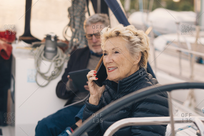 Senior woman talking on mobile phone while sitting by man in yacht