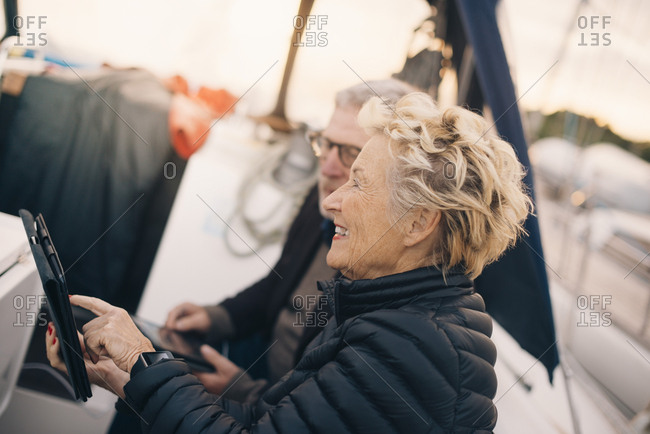Side view of smiling senior woman using digital tablet by man in yacht