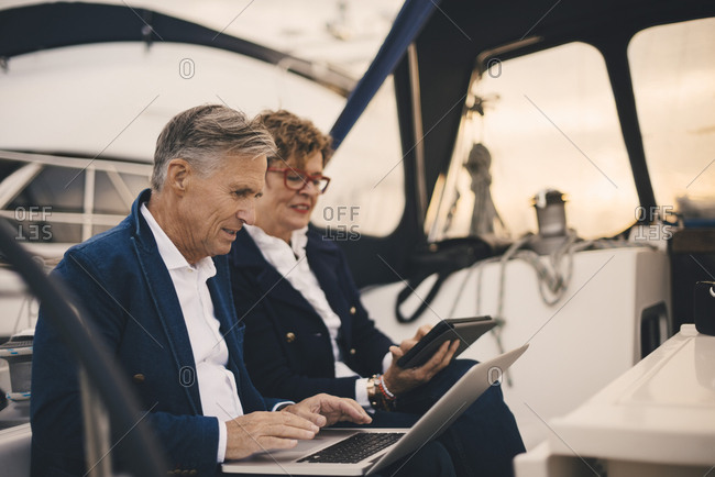 Senior couple using technologies while traveling in yacht during sunset
