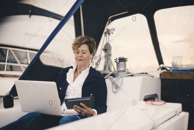 Senior woman using digital tablet and laptop in yacht