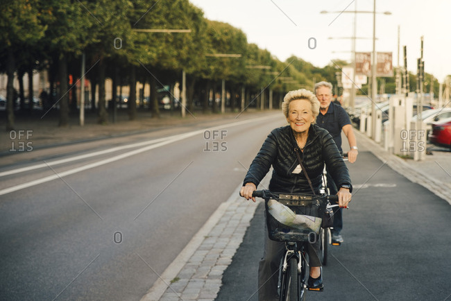 Portrait of smiling senior woman with man riding bicycles on city street