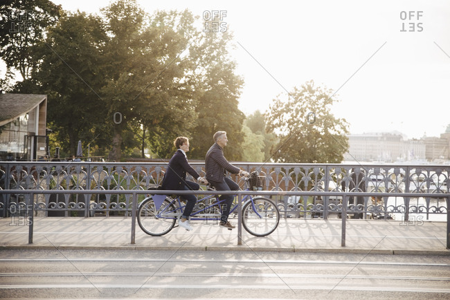 Full length side view of senior couple enjoying tandem bike ride on bridge