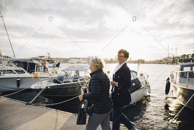 Happy senior women walking on pier by moored boats