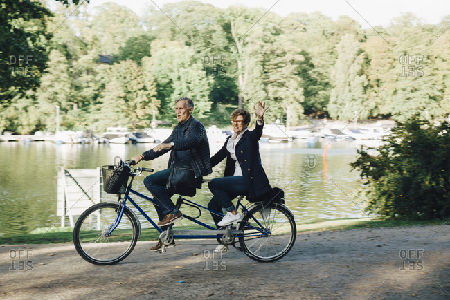 Senior couple enjoying tandem bike ride by pond in park