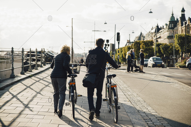 Full length rear view of senior couple with bicycles walking on sidewalk in city