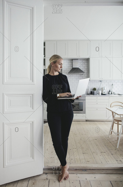 Businesswoman using laptop while standing at doorway in home office