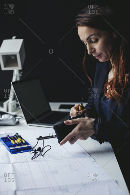 Female businesswoman working on portable hard drive at desk in home office