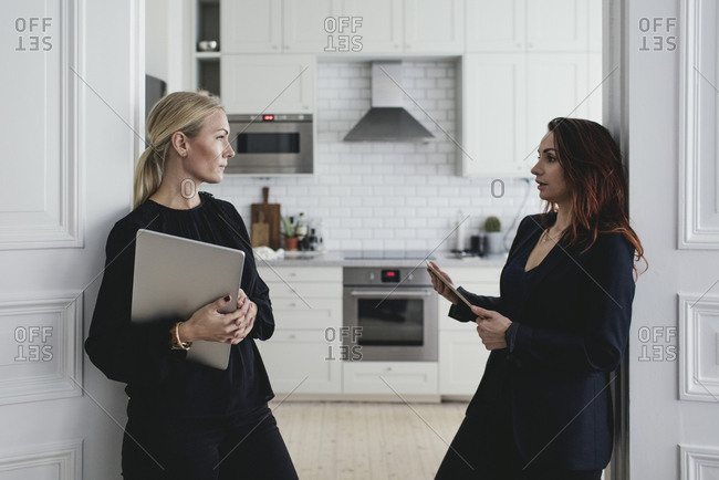 Female colleagues discussing at doorway in home office