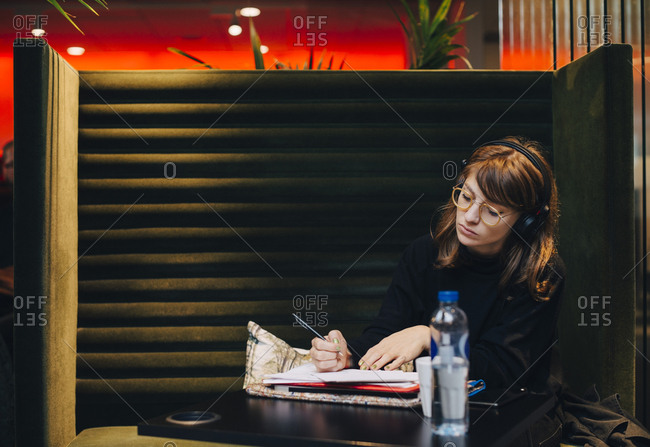 Young businesswoman writing in diary while sitting at office cafeteria