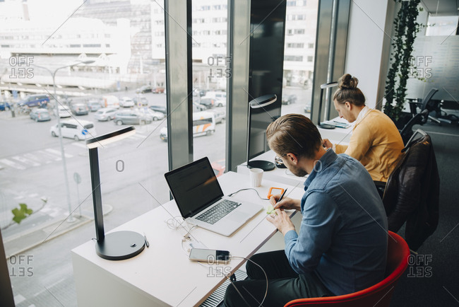Mid adult male colleagues working at office desk in front of window