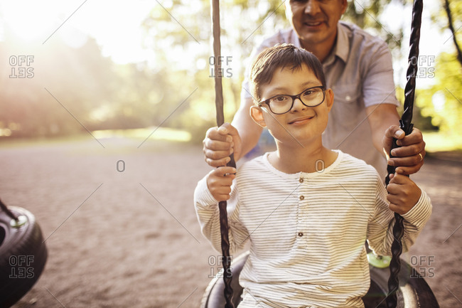 Father swinging disabled son at playground