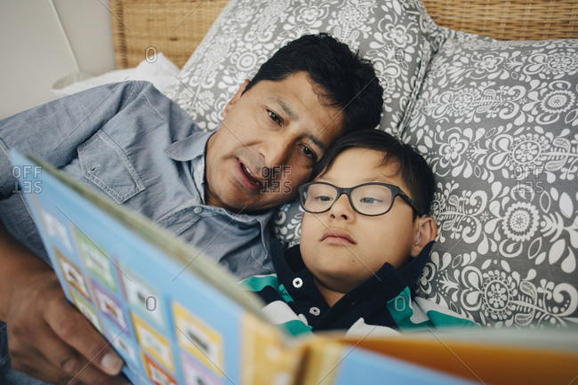Father reading book to son while lying on bed at home